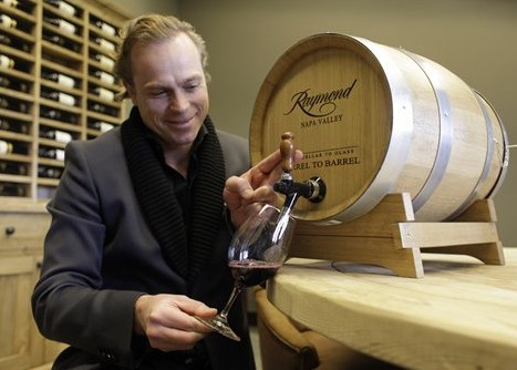 This Friday, Feb. 25, 2011 shows Jean-Charles Boisset, president of Boisset Family Estates, as he draws wine from a barrel-to-barrel dispenser at Raymond Vineyards in St. Helena, Calif.  Boisset Family Estates runs DeLoach Vineyards in the Russian River Valley region of Sonoma County, which has been selling what they call the barrel-to-barrel concept for more than a year, and recently launched the program at the company's St. Helena-based Raymond Vineyards.      (AP Photo/Eric Risberg)