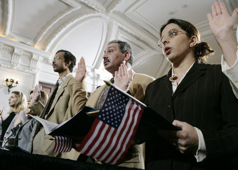 P032706ED-0075 Naturalization ceremony participants raise their hands and hold American flags as they are sworn-in as new U.S. citizens Monday, March 27, 2006, during the Naturalization Ceremony at the Daughters of the American Revolution Administration Building in Washington. President George W.Bush addressed the audience, saying that each generation of immigrants brings a renewal to our national character and adds vitality to our culture. White House Photo by Eric Draper
